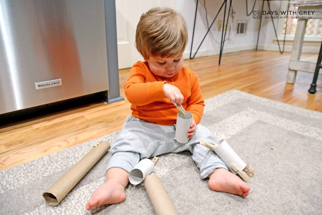 toddler grasping and pulling clothespins