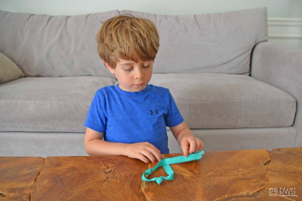 Kindergartener tying knots