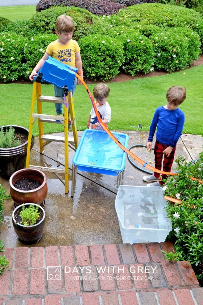 Boys playing outside with water and Hot Wheel tracks.