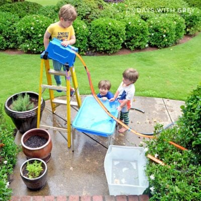 Children building Hot Wheel tracks outside with water